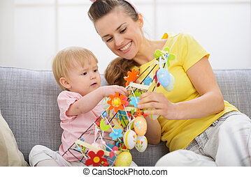 Happy mother and baby making Easter decoration
