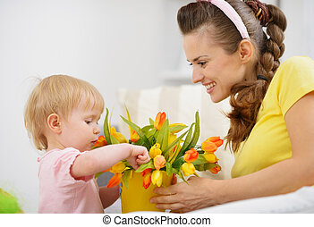 Happy mother and baby making decoration with bouquet of tulips in bucket