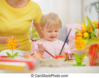 Happy mother and baby making Easter decorations