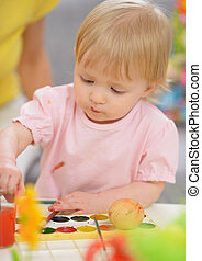 Baby painting on Easter eggs