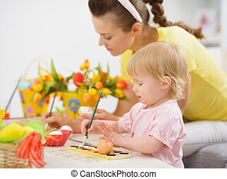Mother and baby making Easter decorations