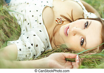 beautiful girl lying down of grass with white dress