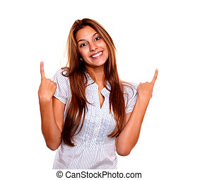 Smiling young woman looking at you and pointing up