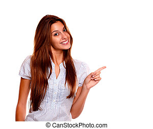 Pretty young woman pointing to her left copyspace - Portrait...
