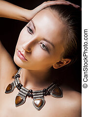 Adorable Woman with Metallic Necklace and Amber. Natural...