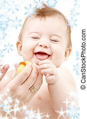 laughing baby boy in mother hands with rubber duck -...