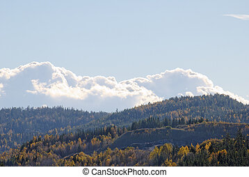 Clouds over Mountains - Billowing clouds over mountains clad...