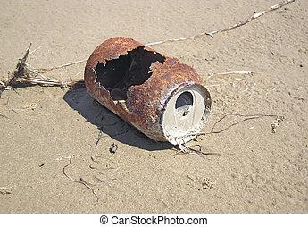 An oxidized tin laid on the sand
