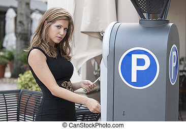 Woman putting money in a parking meter