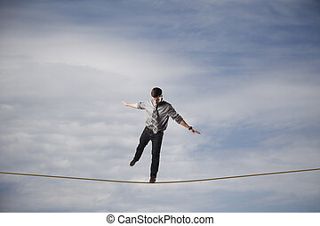 Balancing Act - Young businessman balancing on a rope in the...