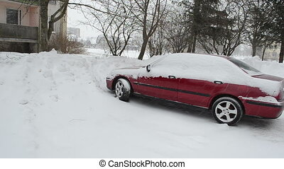 snow fall car parking - blizzard snow fall on red car stand...