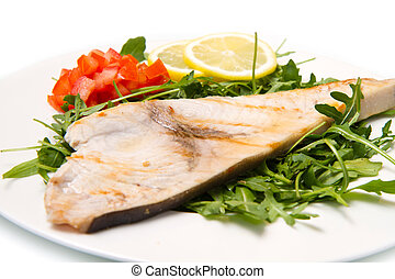 roasted swordfish with lemon, salad and tomatoes on white...