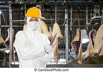 Industrial butcher posing with two filleting knives, wearing...