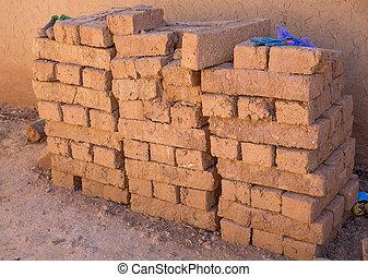 Adobe bricks - Handmade red and brown adobe bricks stacked...
