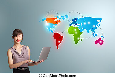 Young woman holding a laptop and presenting colorful world...