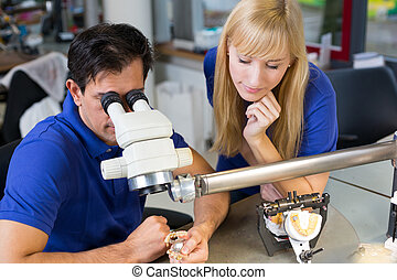 Dental technicians working on microscope - Dental...