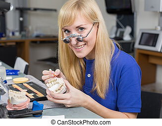 Dental lab technician applying porcelain to dentition mold -...
