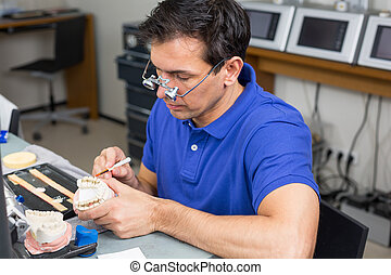 Dental lab technician appying porcelain to mold - Dental lab...