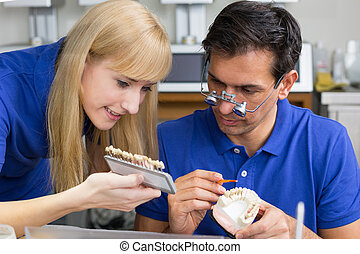 Two dental technicians with colour samples choosing the...