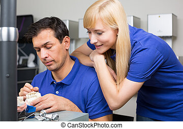 Woman watching dental technician applying porcelain