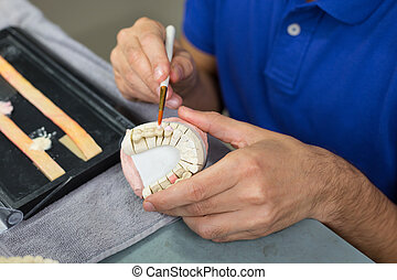 Closeup of dental technician applying porcelain - Closeup of...
