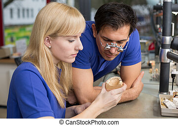 Dental technician showing a prosthesis to a collegue -...