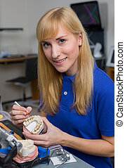 Dental lab technician applying porcelain to dentition mold...