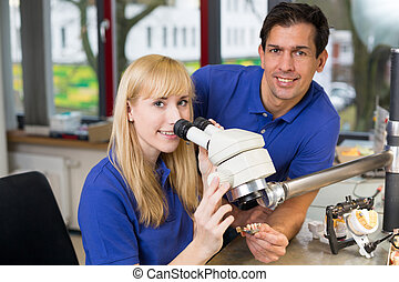 apprentice and dental technician at microscope - apprentice...