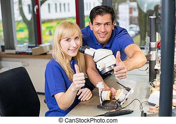 Dental technicians showing thumbs up - Dental technicians...