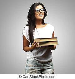 portrait of young girl holding books over grey background