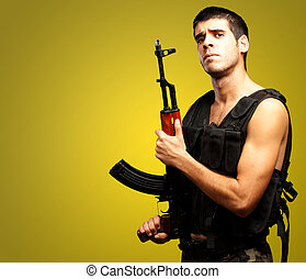 Portrait Of Soldier Holding Gun against a yellow background