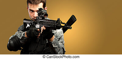 Portrait Of A Soldier Holding Gun against an orange...