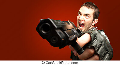 Angry Soldier Holding Gun against a red background