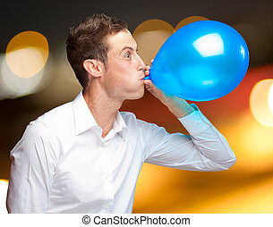Portrait Of Young Man Blowing A Balloon - Portrait Of Young...