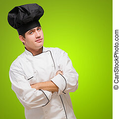 Young Chef With Hands Folded against a green background