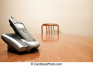 Modern cordless phone sitting on an empty table