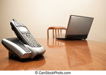 Cordless phone and laptop on table