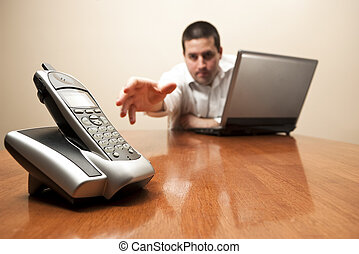 Businessman reaches for cordless telephone
