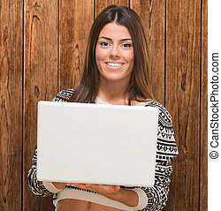 Young Woman Holding Laptop against a wooden background