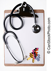 Stethoscope and medicine on clipboard with blank sheet of...