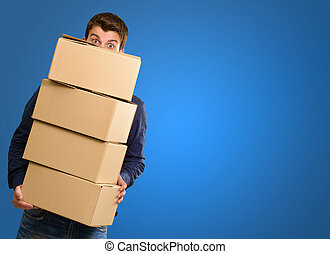 Man holding cardboard boxes on blue background