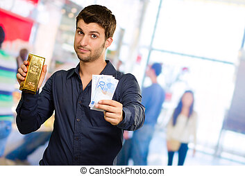 Young Man Holding Gold Bar And Euro Currency, Indoors