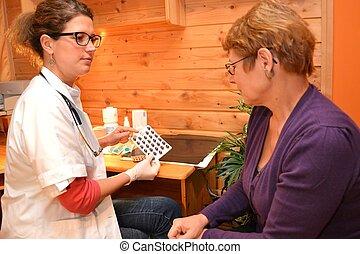 Aerztin zeigt Patientin Tabletten - Patientin laesst sich...