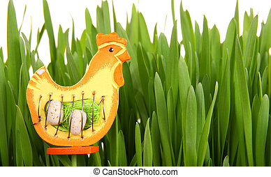 Easter decoration made with wooden hen and green grass
