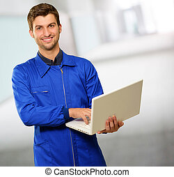 Happy Young Technician Working On Laptop, Indoor
