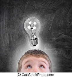 Boy with Light Bulb Idea Looking Up - A young school boy is...