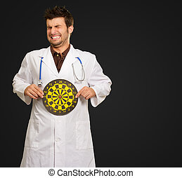Scared Young Doctor Holding Bulls Eye On Black Background