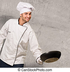 Portrait Of Male Chef Holding Pan On Wall