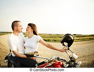 Young biker couple on the country road against the sky