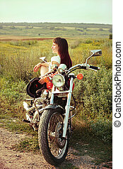 Young biker woman on the country road against the sky